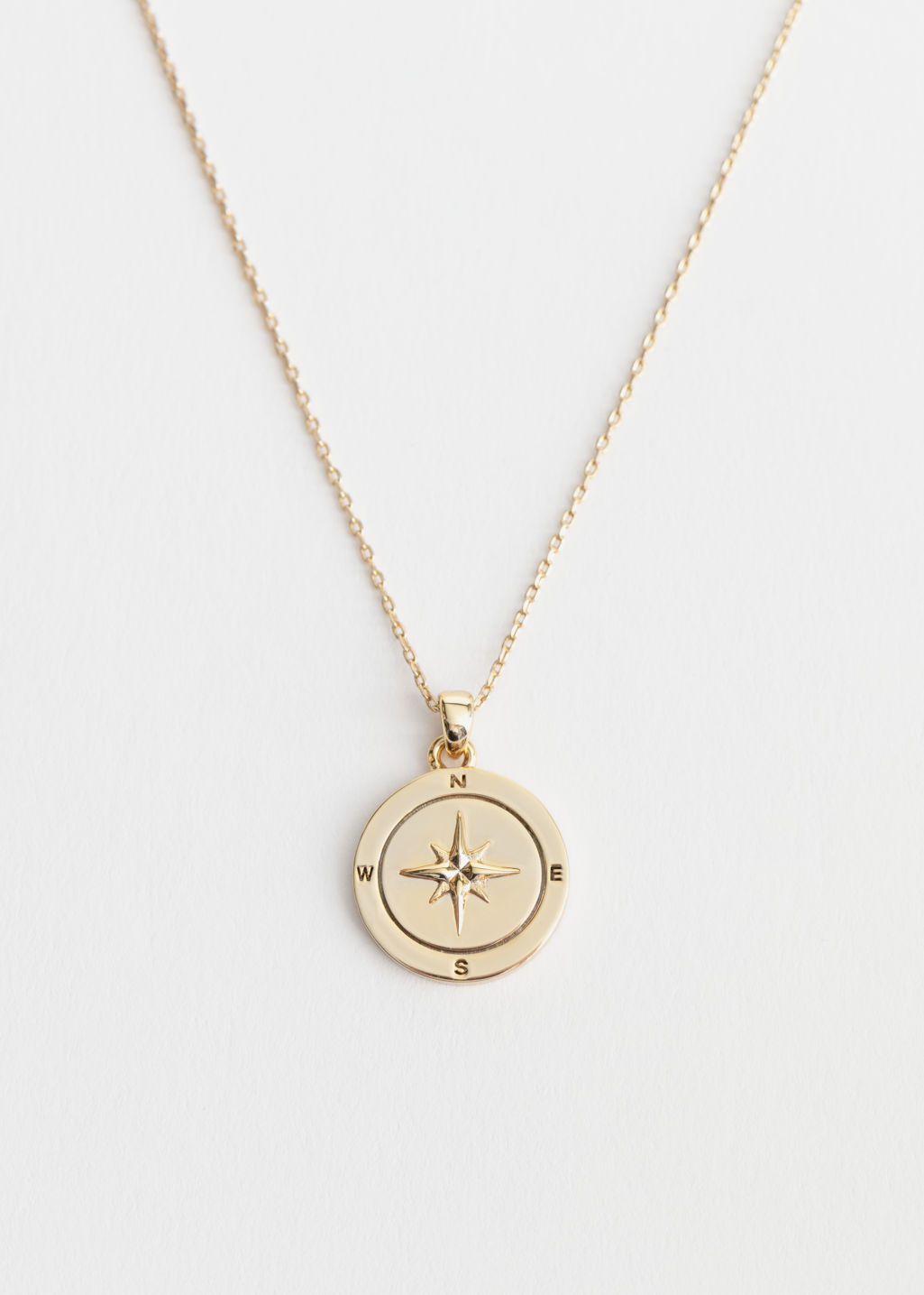 Front image of Stories compass pendant necklace in gold