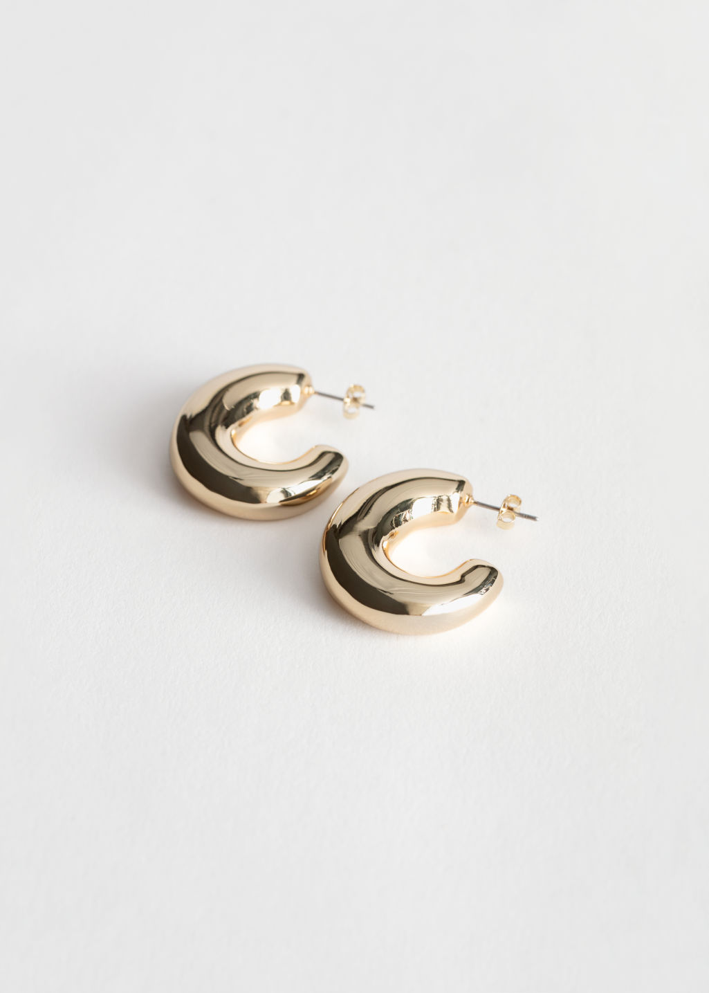 Front image of Stories chunky hoop earrings in gold