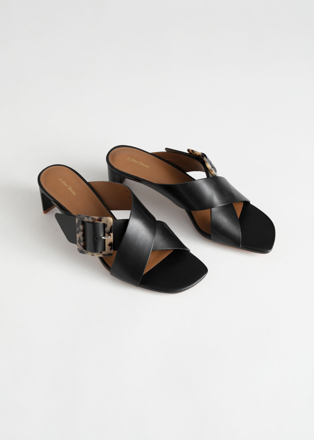 Back image of Stories criss cross tortoise buckle mules in black