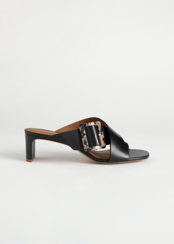 Front image of Stories criss cross tortoise buckle mules in black