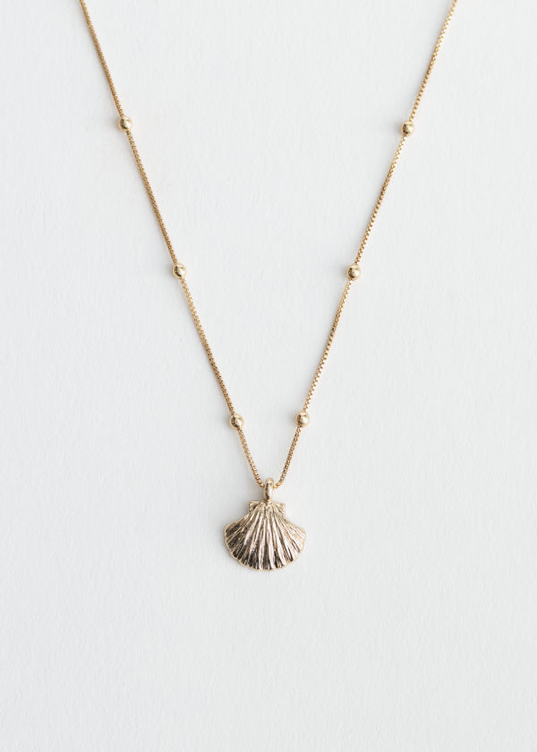 Front image of Stories studded seashell charm necklace in gold