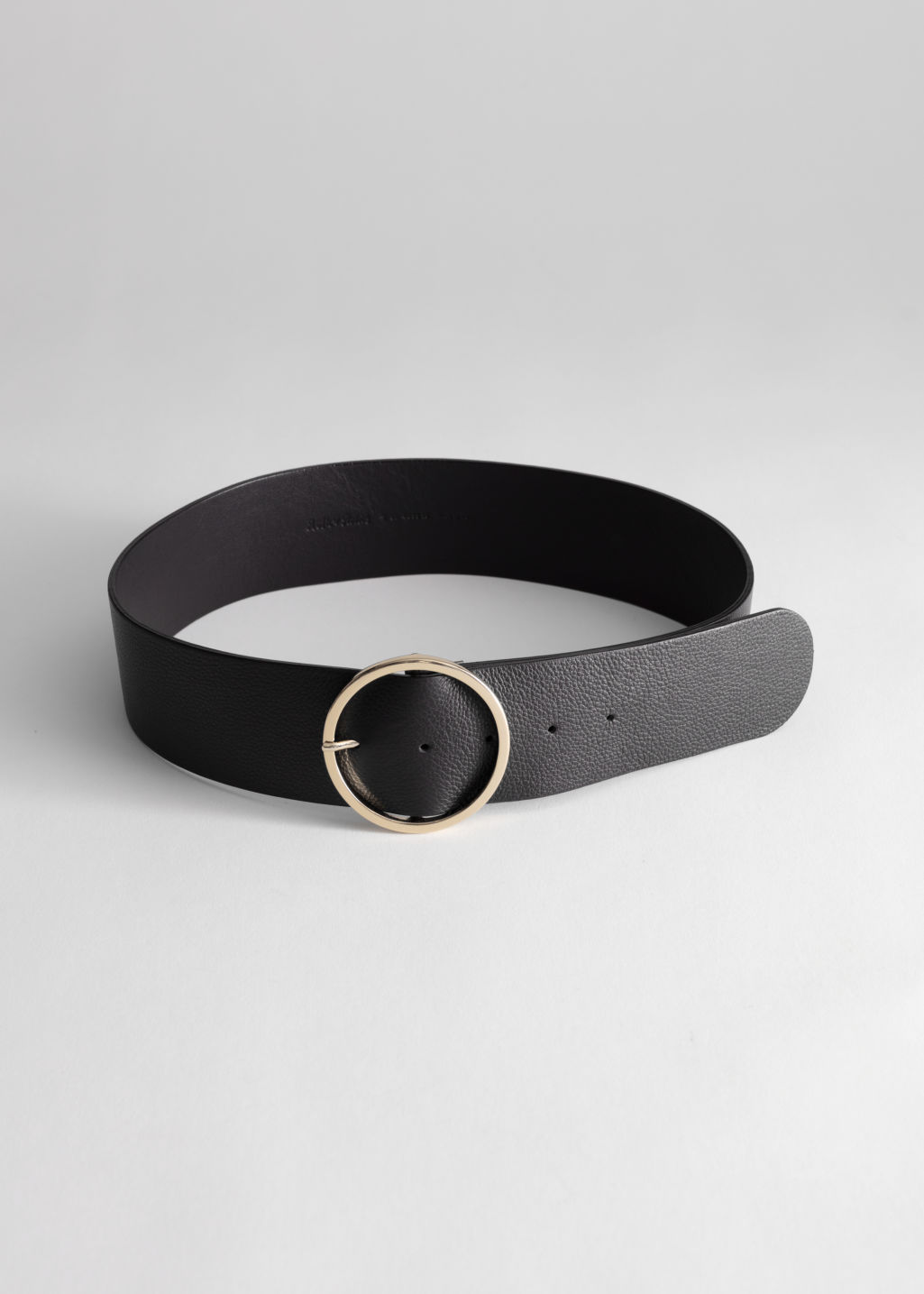 Front image of Stories circle buckle leather belt in black