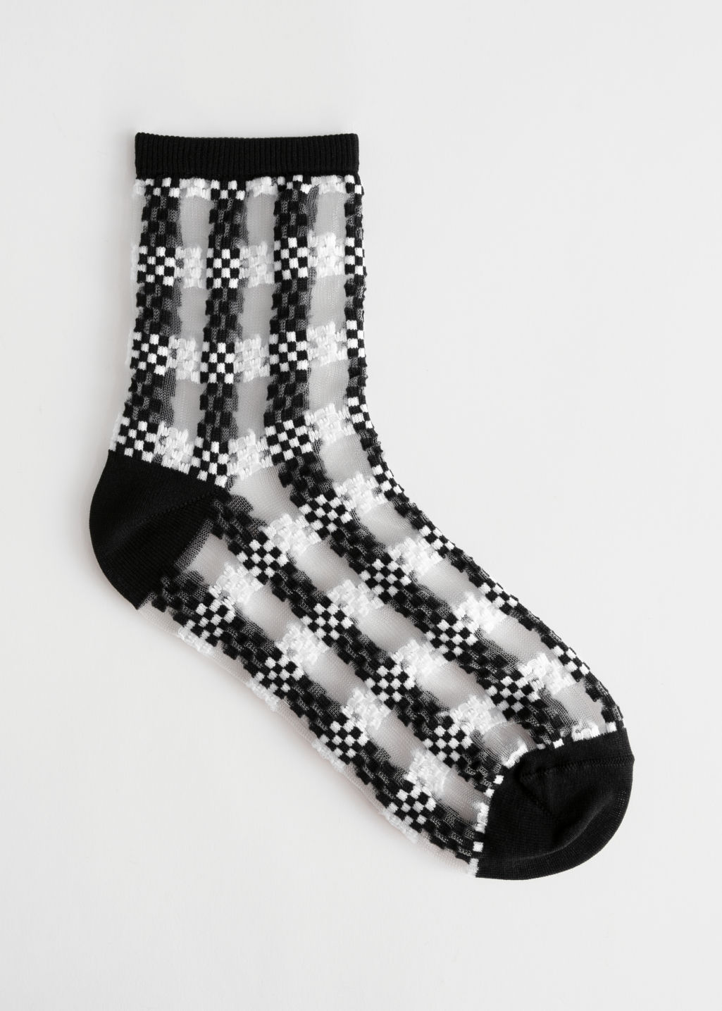 Front image of Stories sheer checkered ankle socks in black