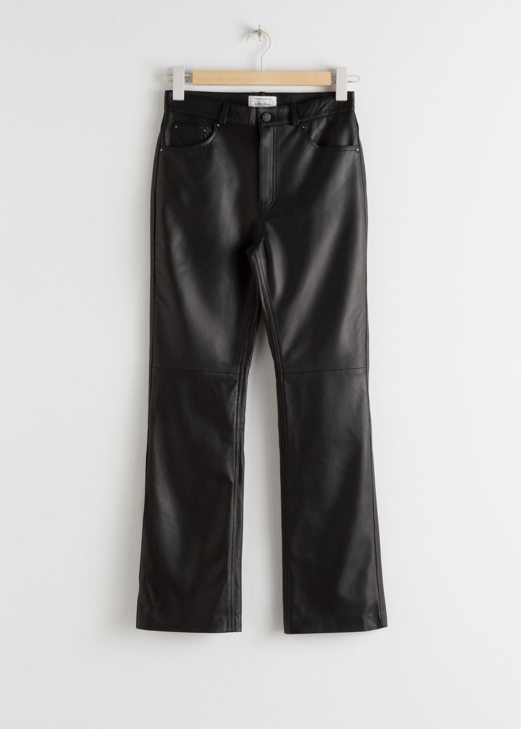 Front image of Stories leather kick flare trousers in black