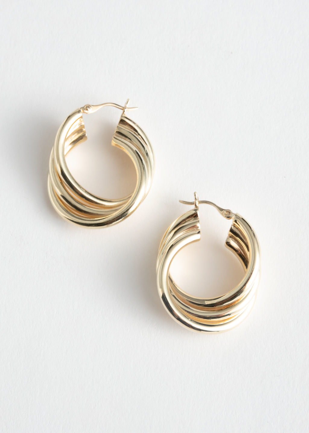 Front image of Stories trio twisted hoop earrings in gold