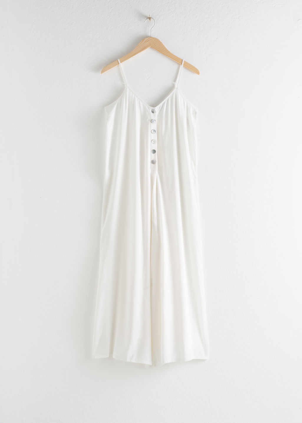 Front image of Stories relaxed spaghetti strap jumpsuit in white
