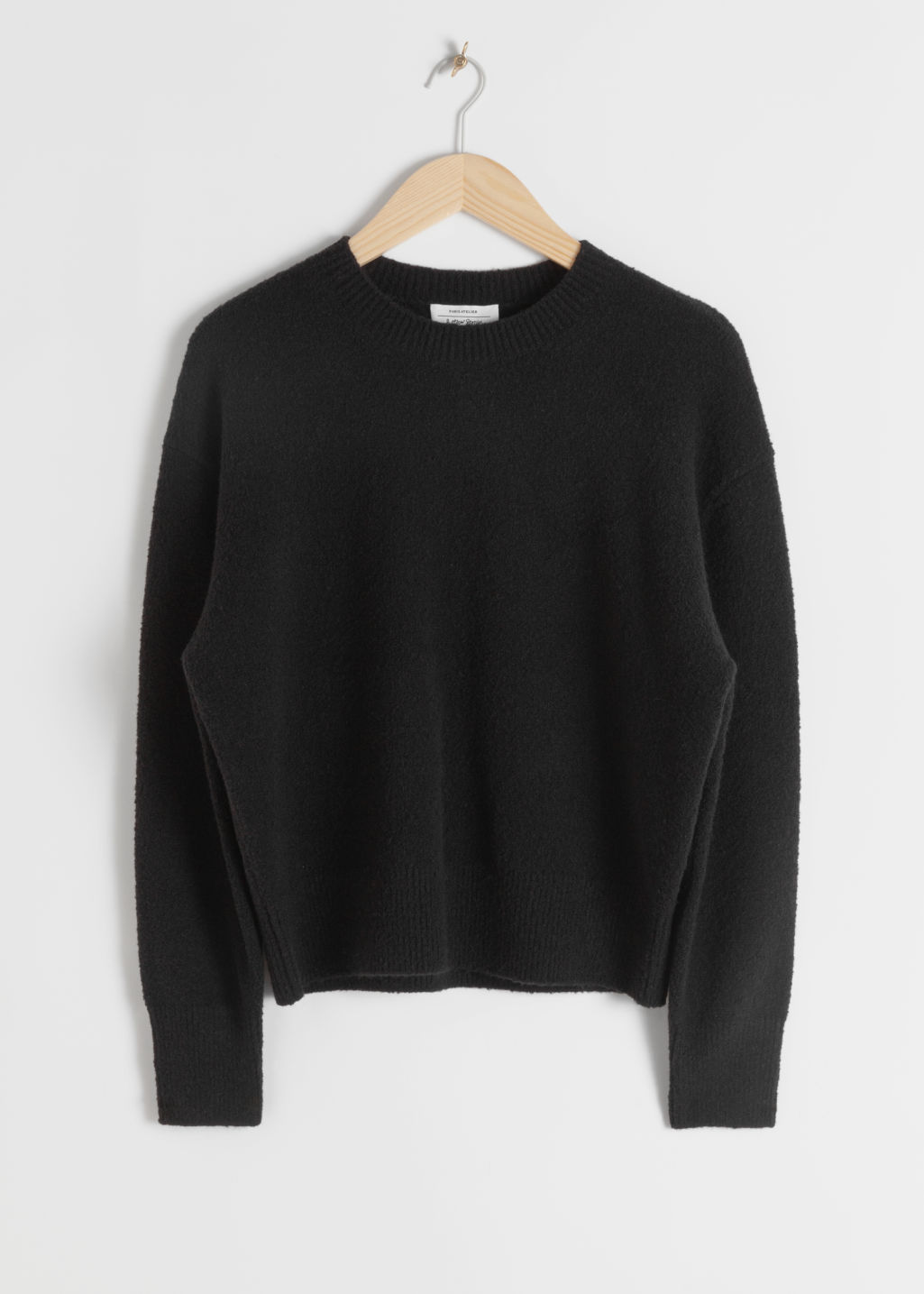 Front image of Stories textured knit relaxed sweater in black
