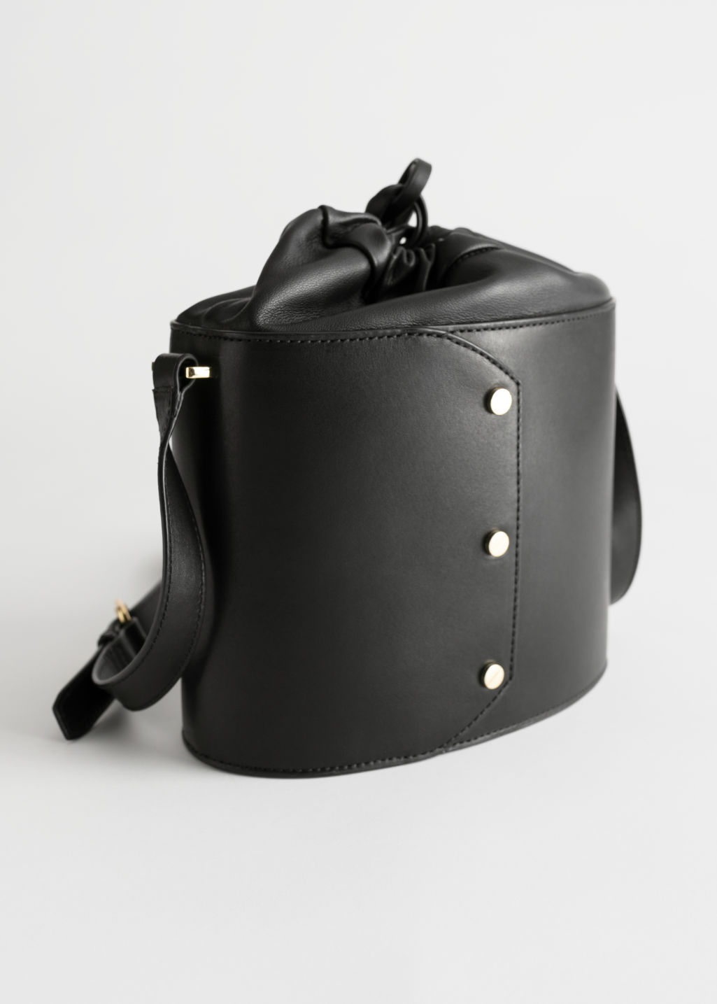Front image of Stories small leather bucket bag in black