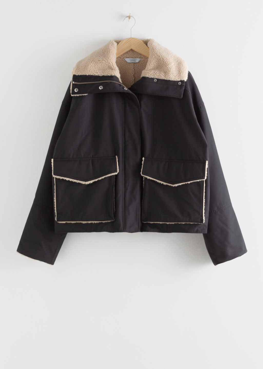 Front image of Stories oversized faux shearling lined jacket in black