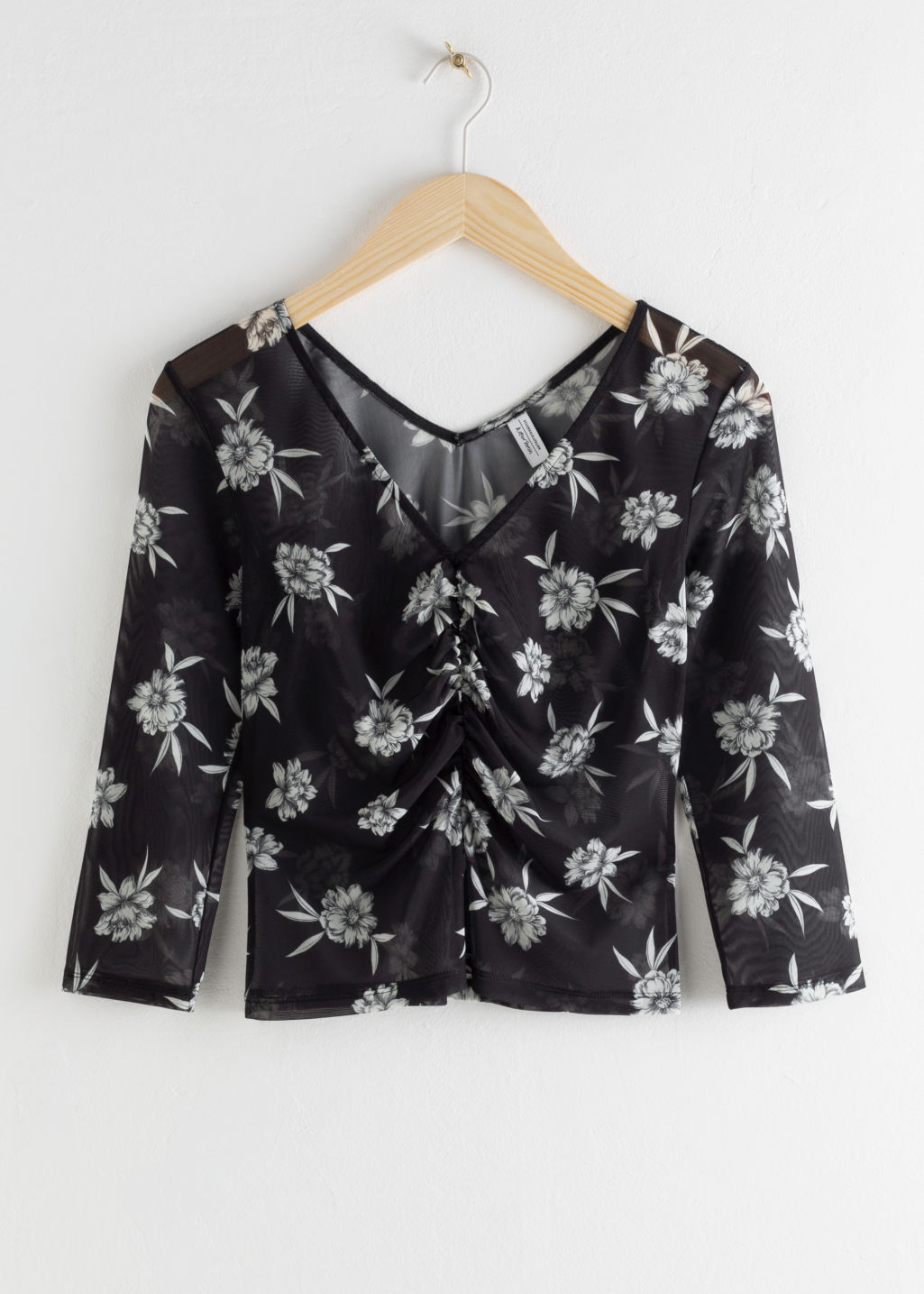 Front image of Stories sheer floral ruched top in black