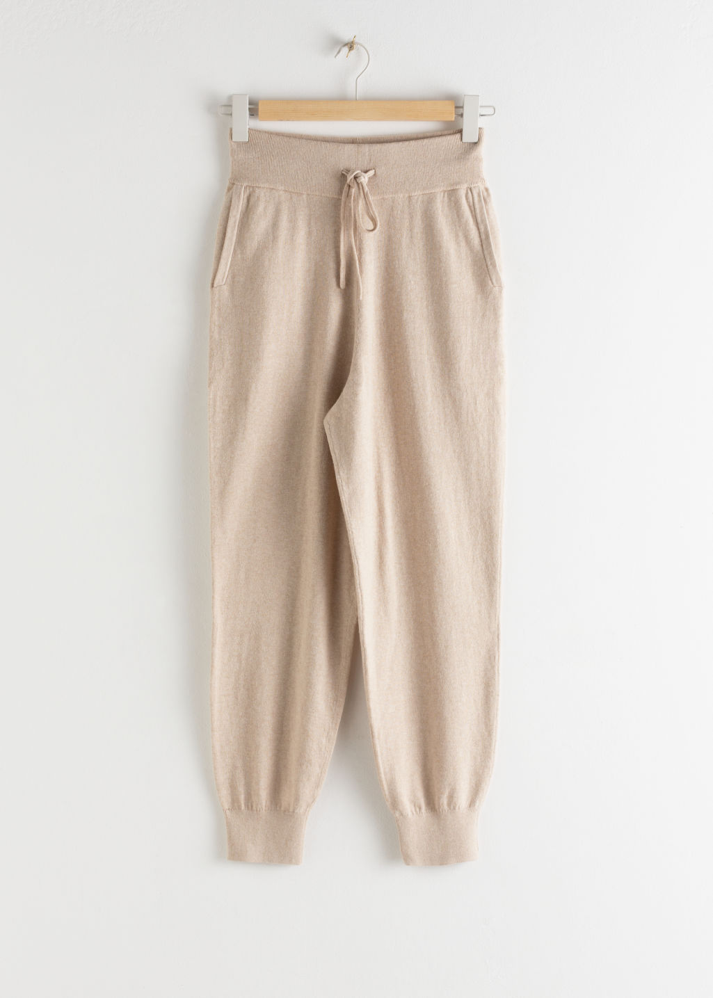 Front image of Stories cashmere blend jogger trousers in beige