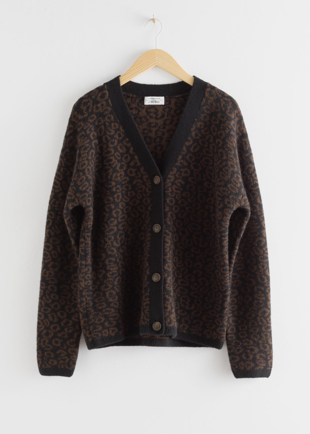 Front image of Stories leo jacquard wool blend cardigan in black