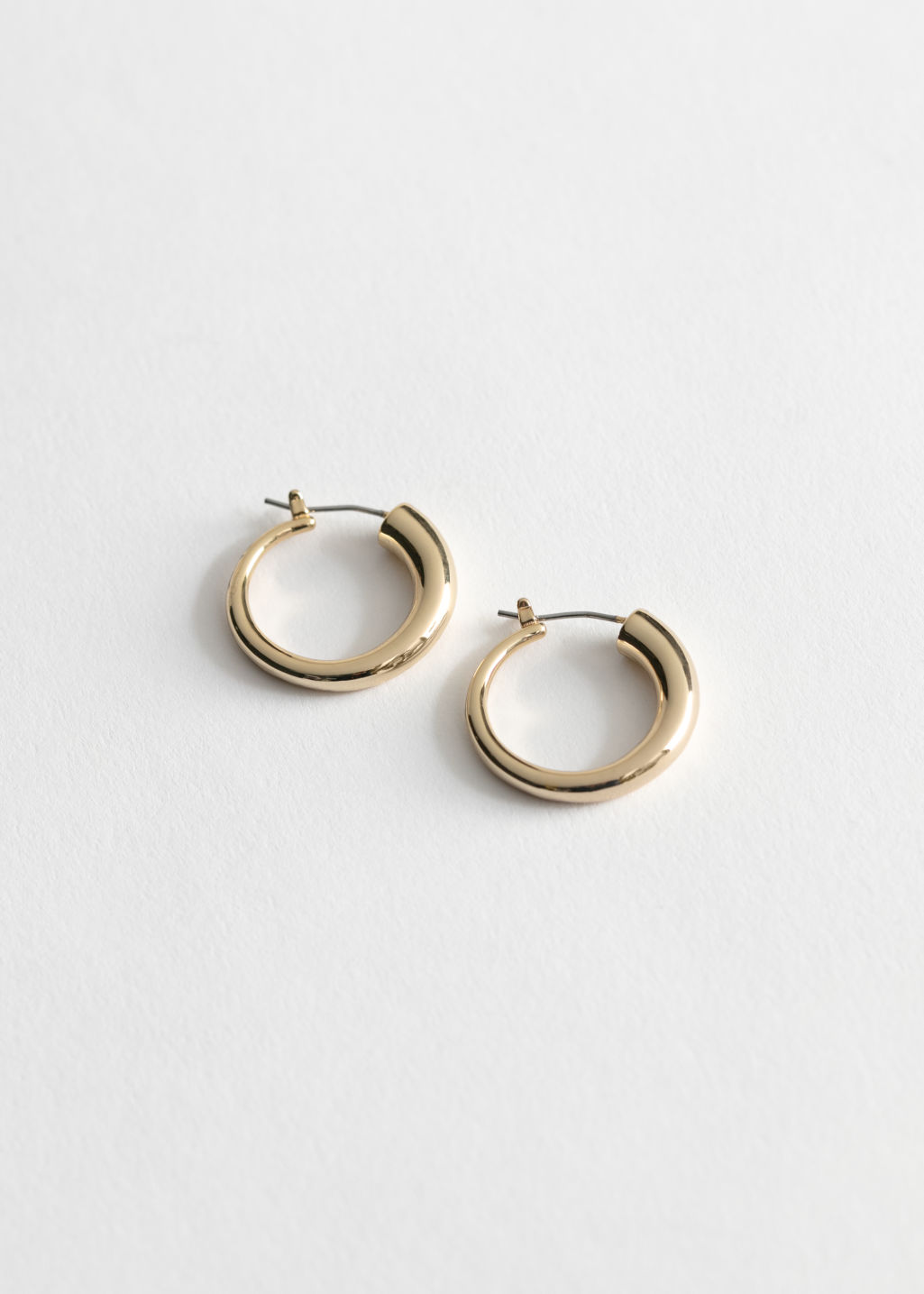 Front image of Stories glossy trumpet mini hoops in gold