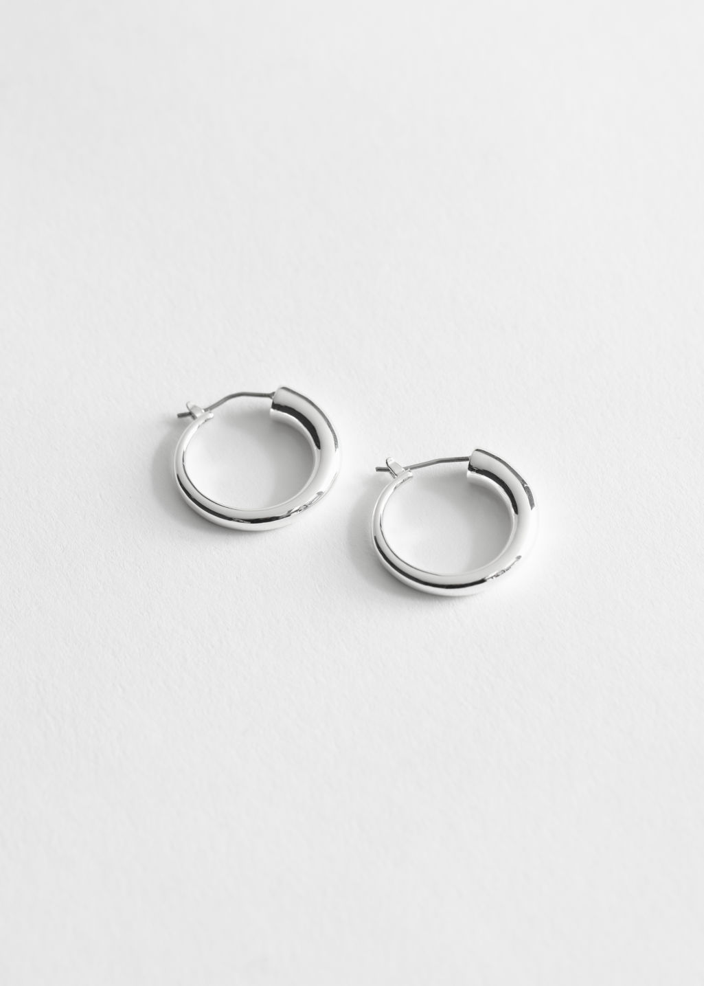 Front image of Stories glossy trumpet mini hoops in silver