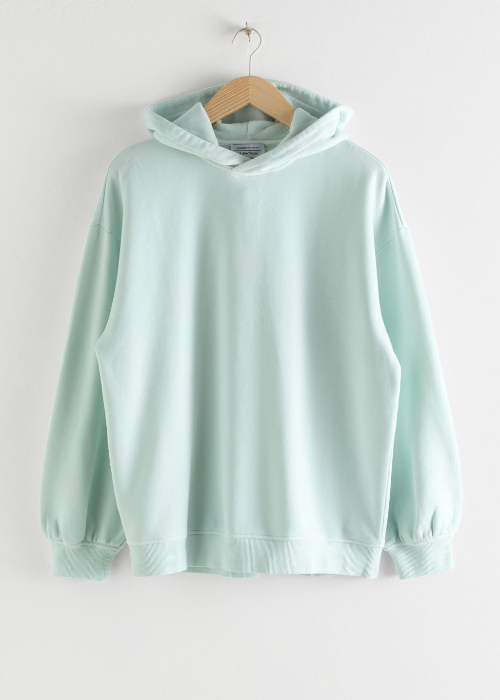 Front image of Stories oversized hooded sweatshirt in green