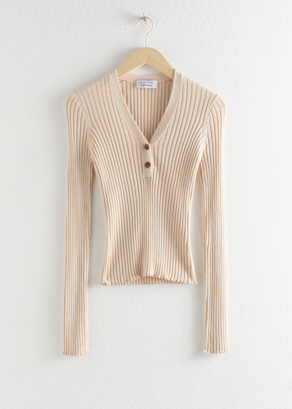 Front image of Stories ribbed v-neck knit top in beige