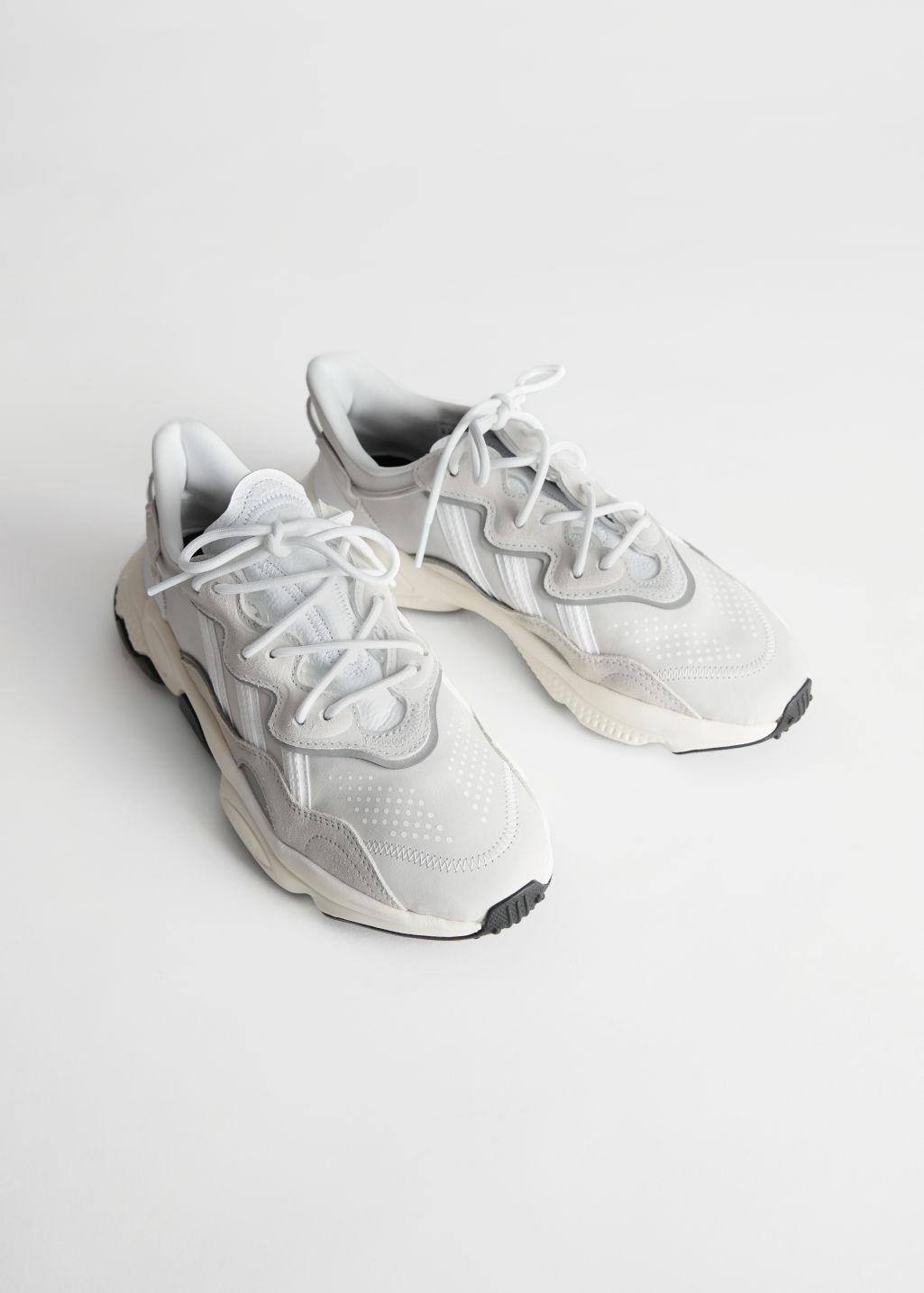 StillLife Front Image of Stories adidas OZWEEGO in White