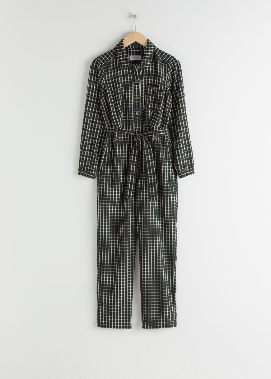 Front image of Stories lyocell belted plaid jumpsuit in black
