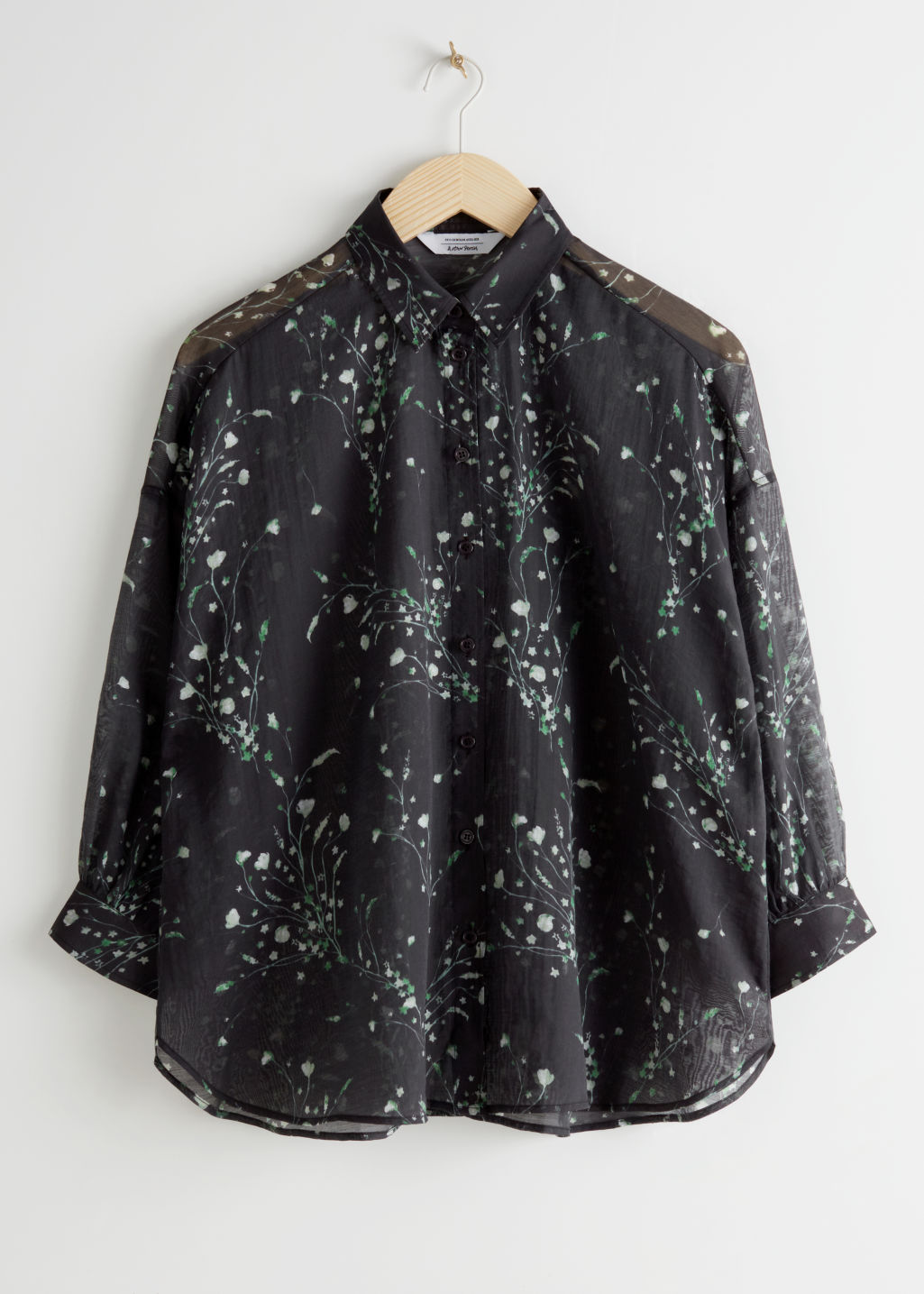Front image of Stories semi sheer floral print blouse in black