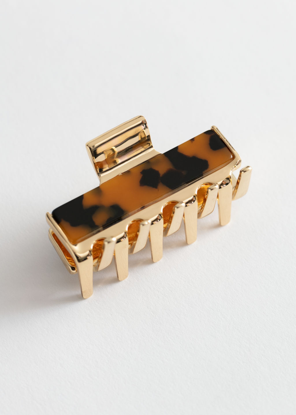 Front image of Stories tortoise gold hair clip in gold