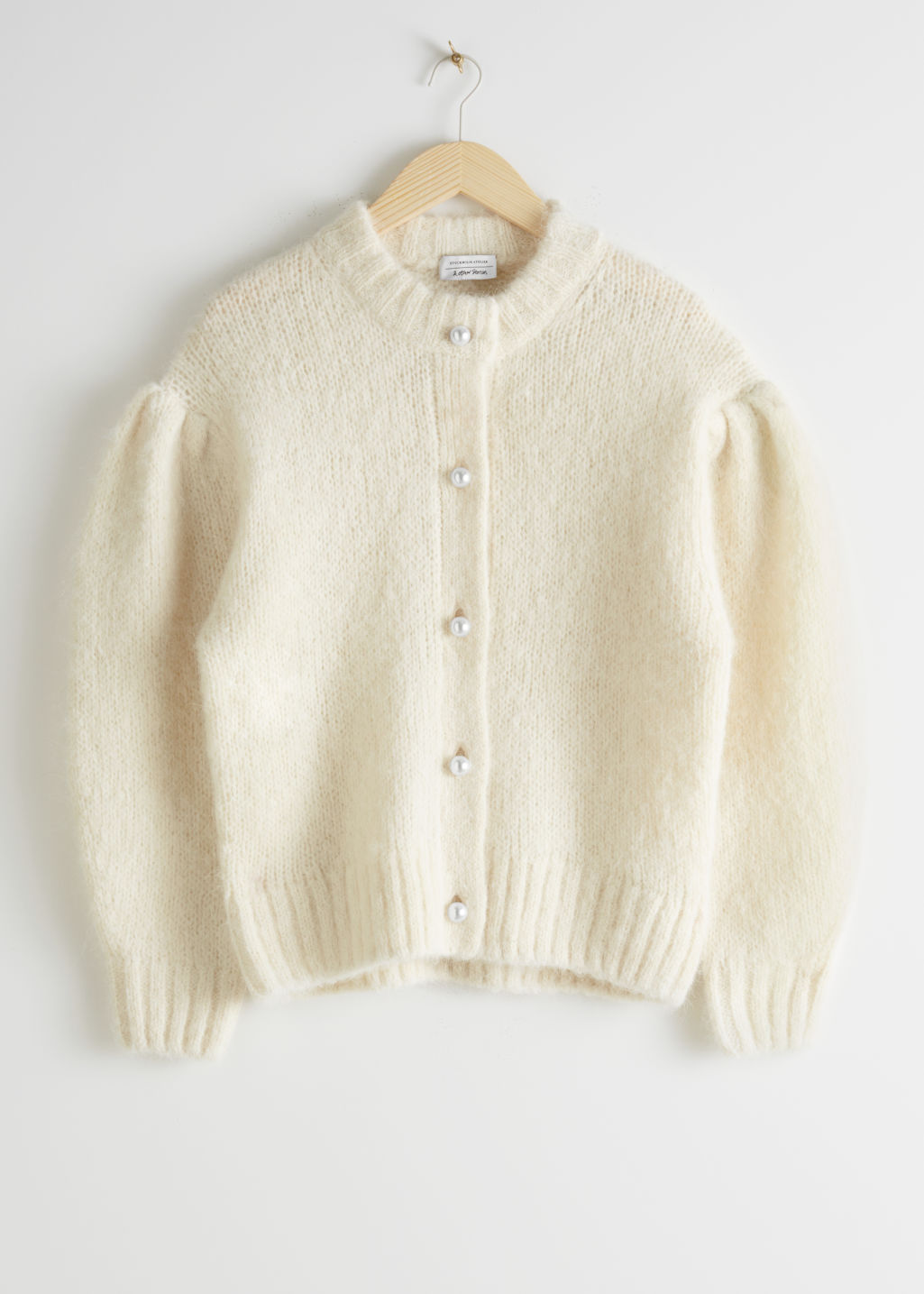 Front image of Stories pearl button puff sleeve cardigan in white