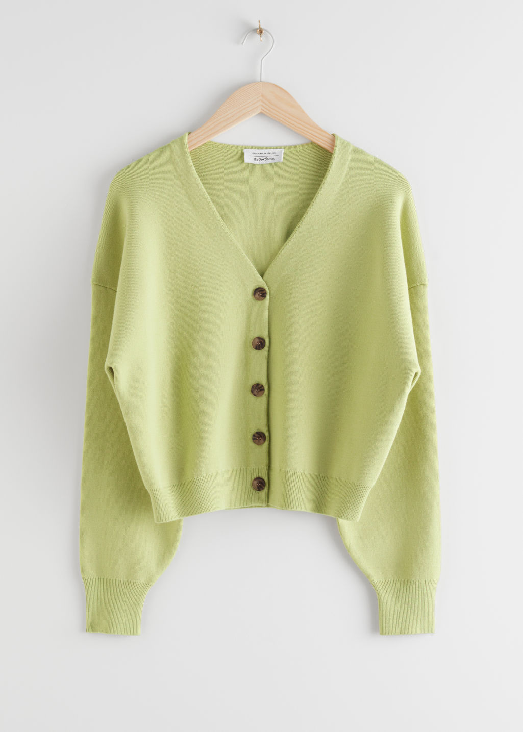 Front image of Stories boxy plunging v-cut cardigan in green