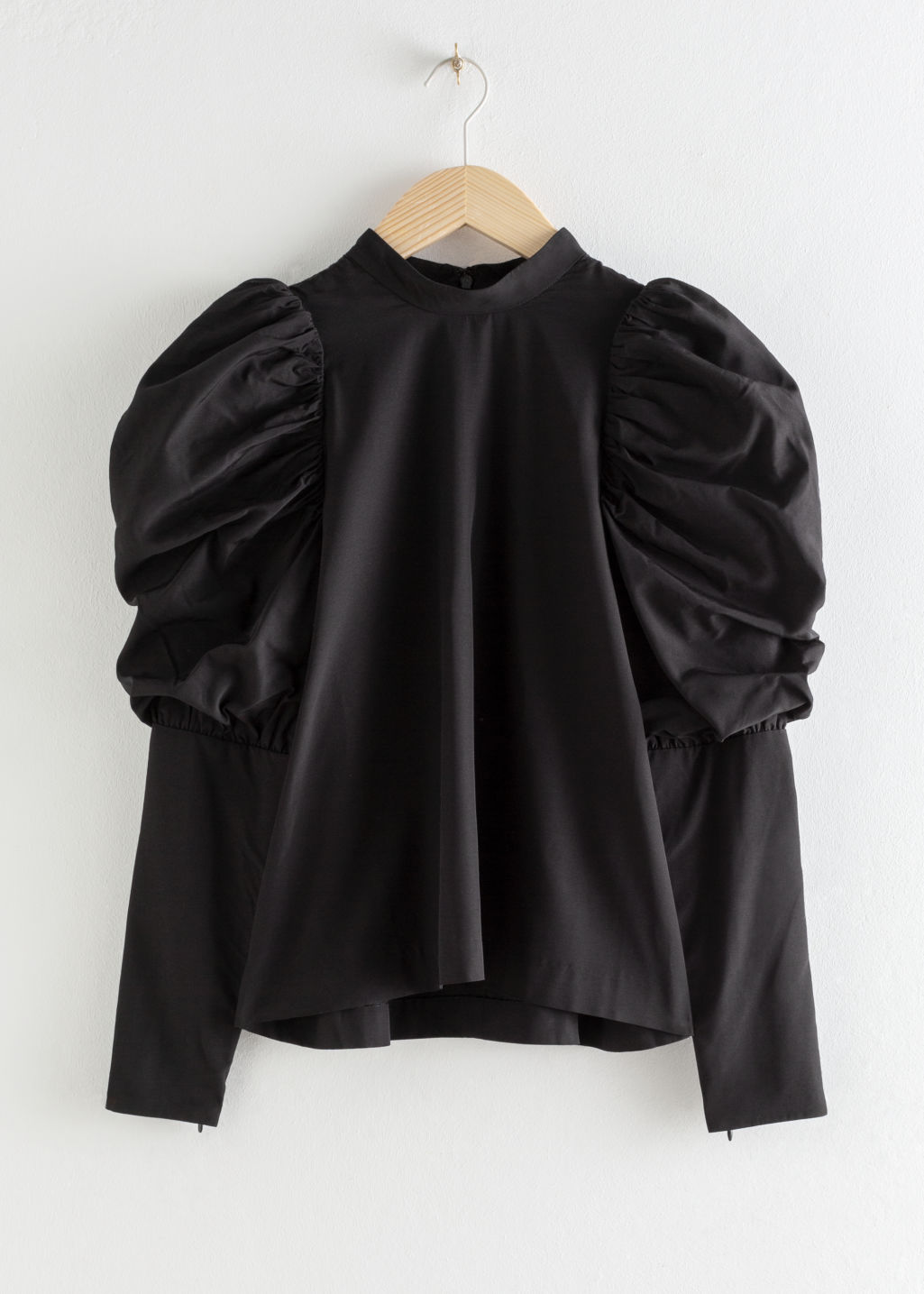 Front image of Stories puff shoulder mock neck blouse in black