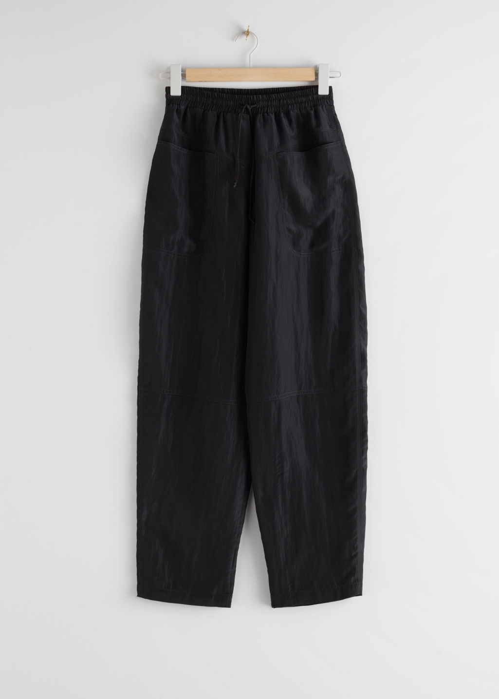 Front image of Stories nylon wide leg drawstring trousers in black