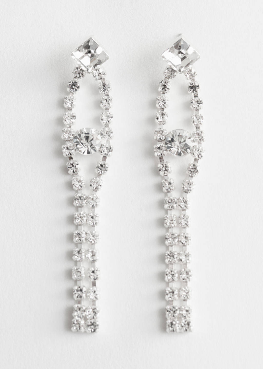Front image of Stories dangling diamanté earrings in white