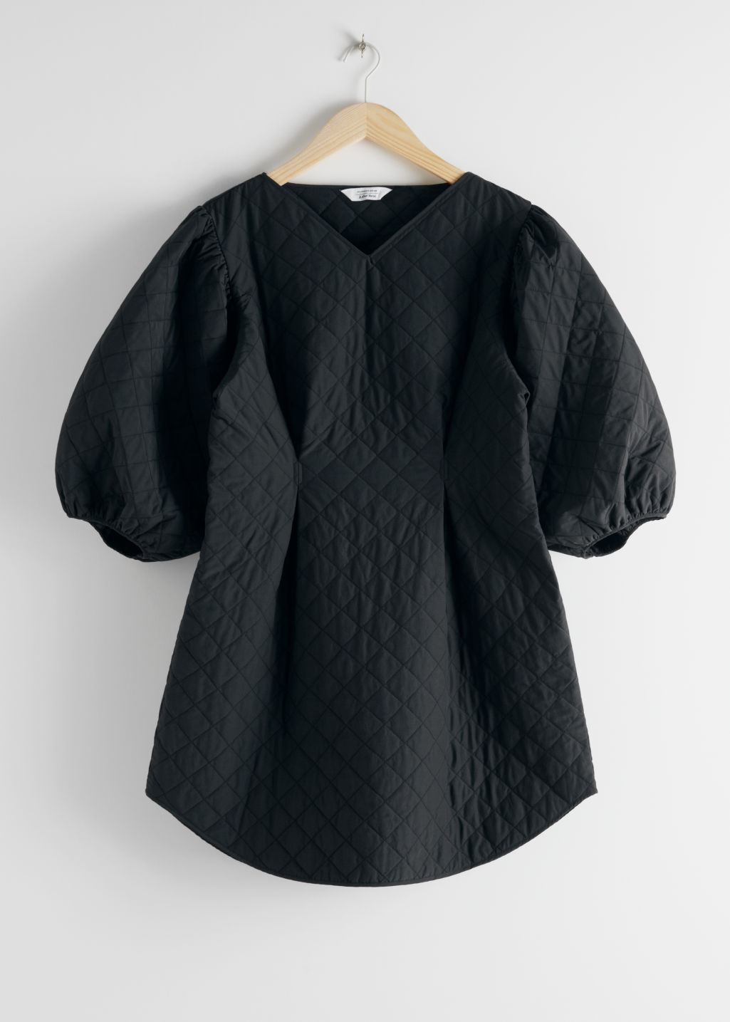 Front image of Stories quilted voluminous puff sleeve dress in black