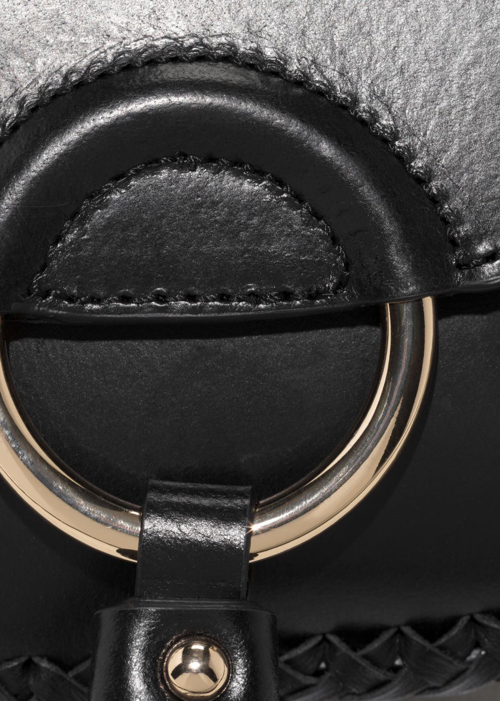 Detailed image of Stories ring & tassel leather mini-saddle bag in black