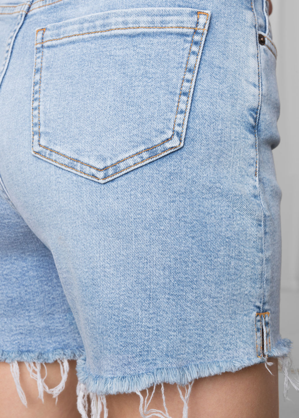 Detailed image of Stories raw hem denim shorts in blue