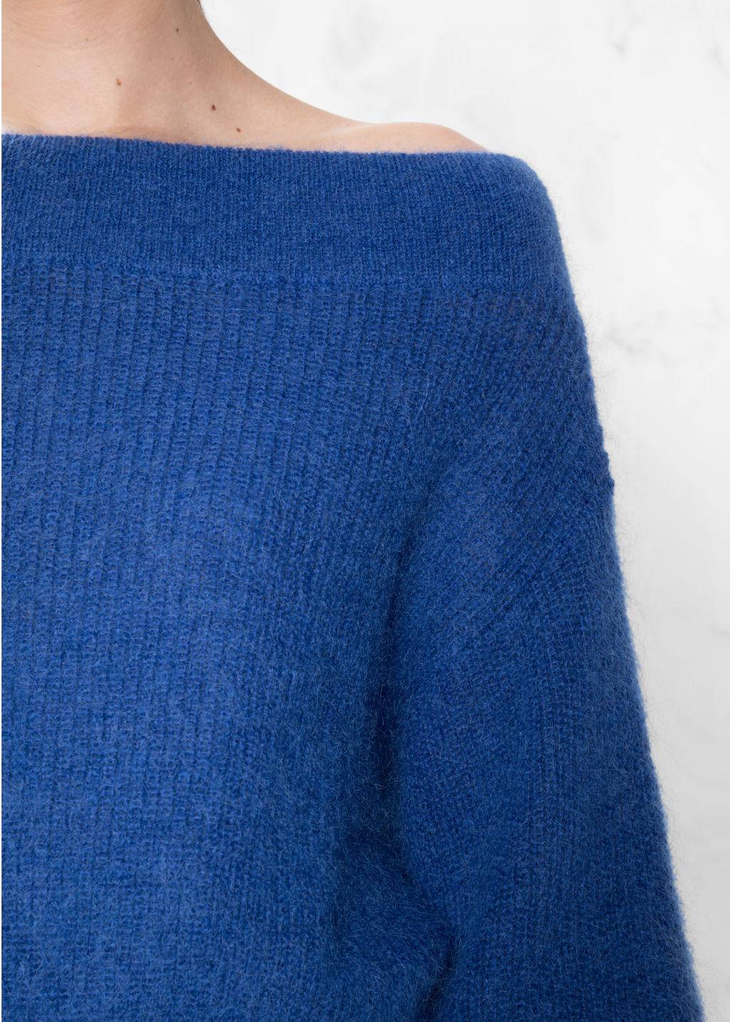 Detailed image of Stories knit off-shoulder sweater in blue
