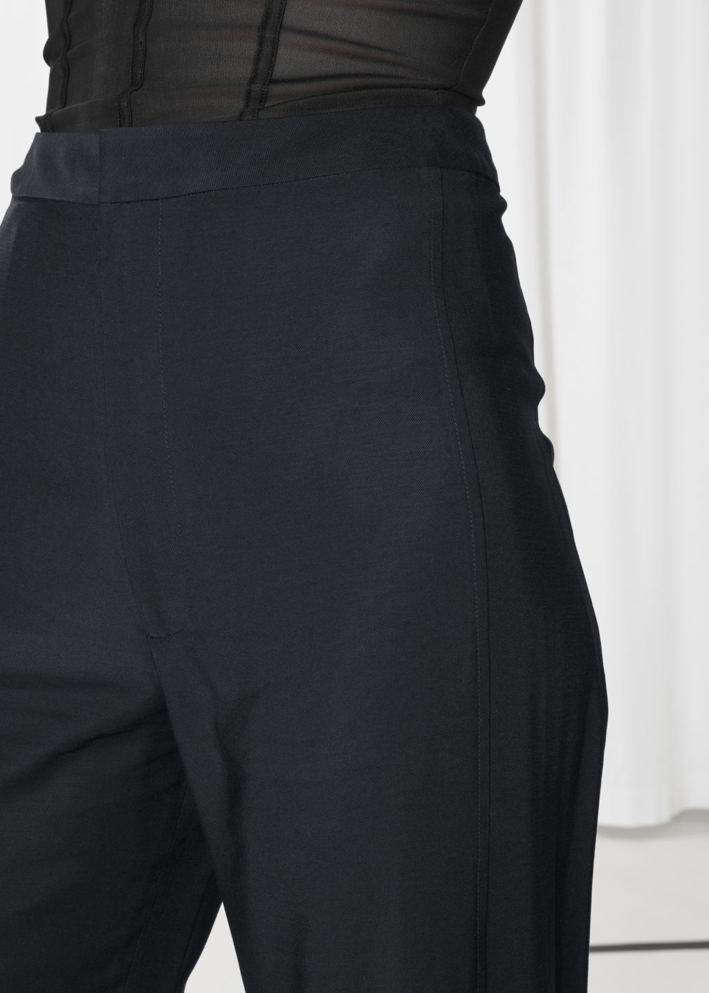 Detailed image of Stories front slit flare trousers in black