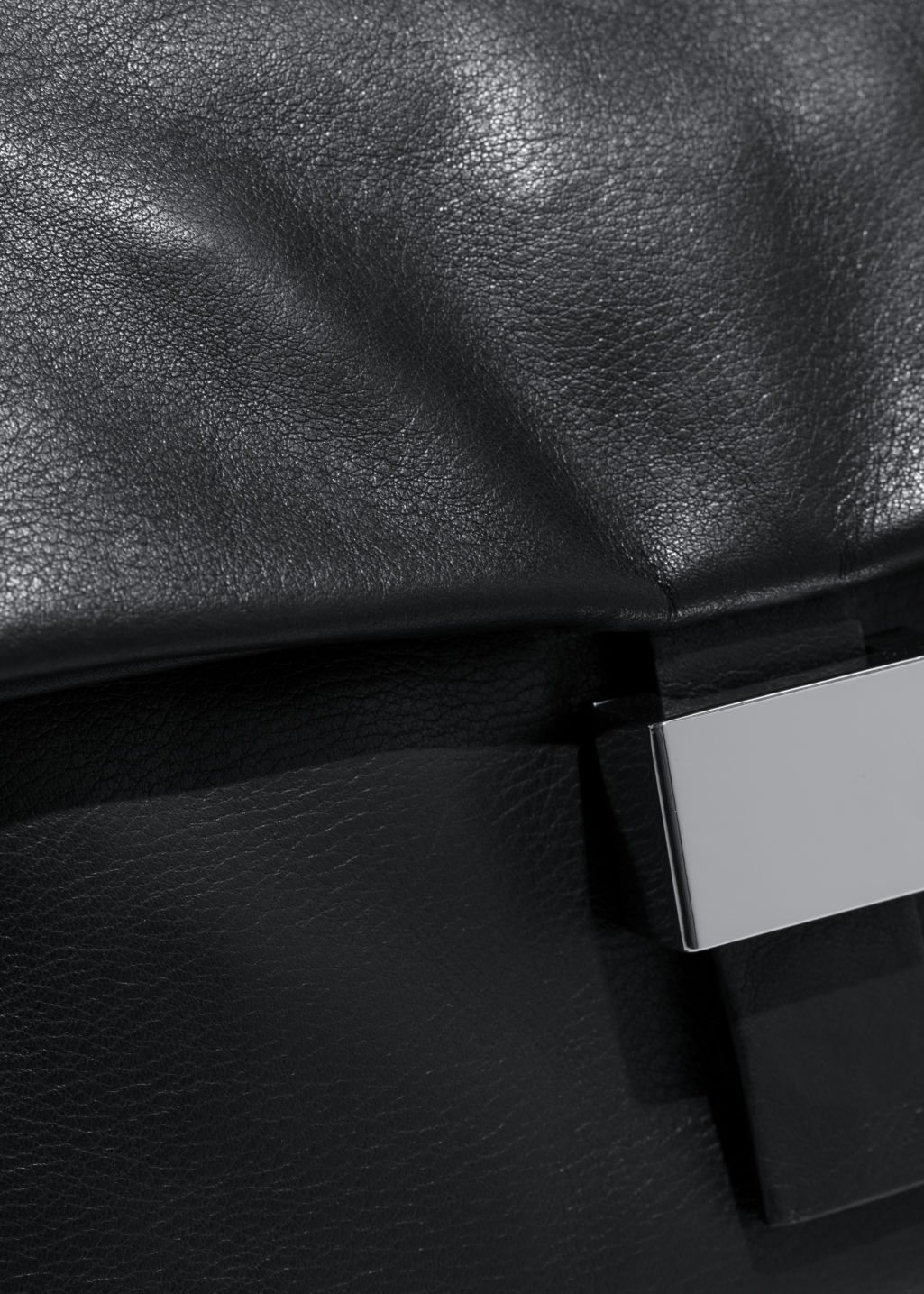 Detailed image of Stories leather fold-over bag in black